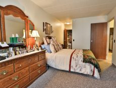 The closet, large dresser, and bed in the master bedroom